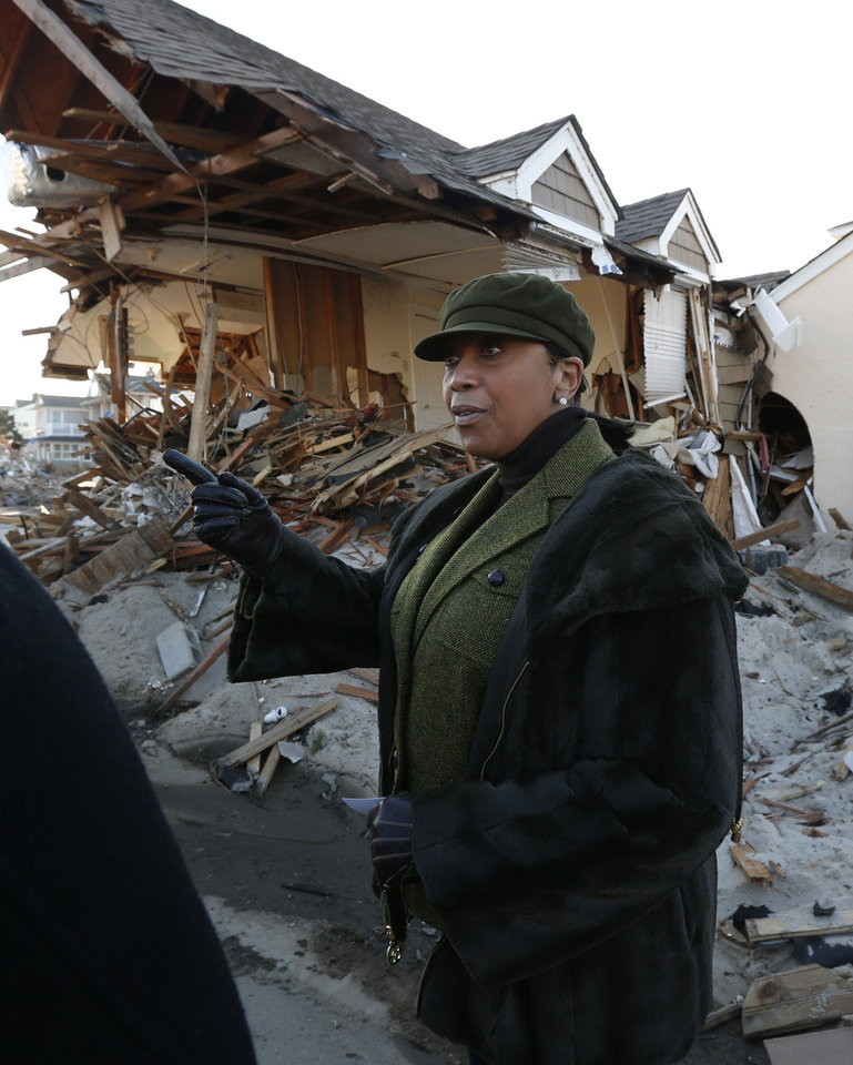 New Jersey State Assembly Speaker Sheila Oliver stands next to a home damaged by Superstorm Sandy, Thursday, Nov. 29, 2012, in Mantoloking, N.J. The New Jersey General Assembly took a tour of areas hit a month after the storm. (AP Photo/Julio Cortez)