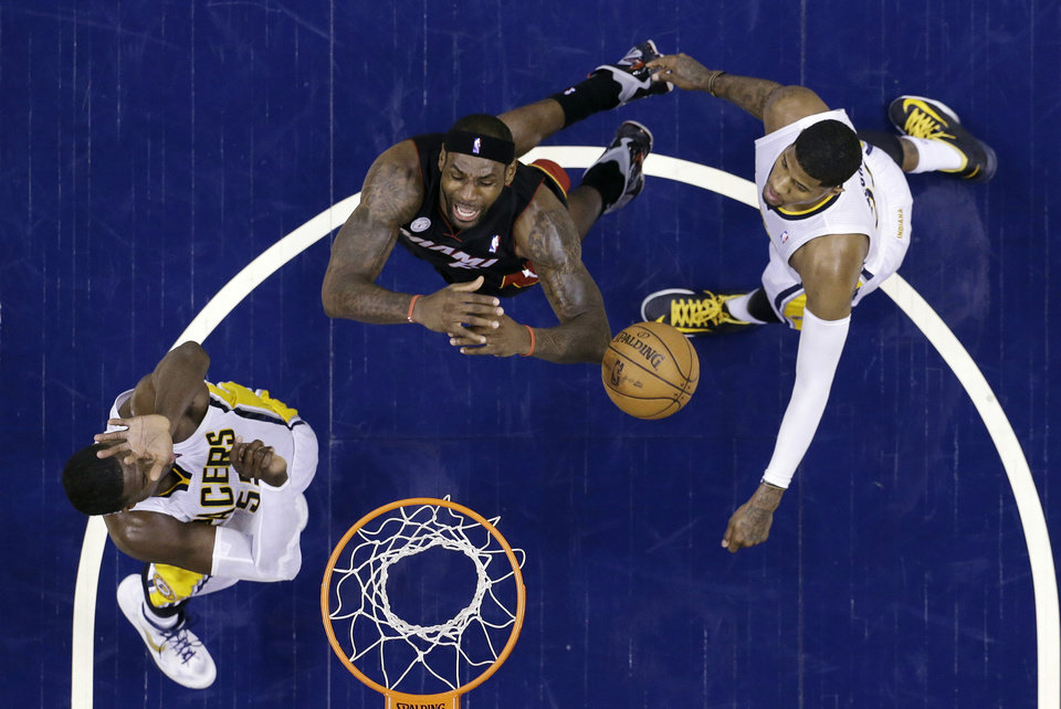Miami Heat's LeBron James, center, goes to the basket against Indiana Pacers' Roy Hibbert, left, and Paul George during the first half of Game 3 of the NBA Eastern Conference basketball finals in Indianapolis, Sunday, May 26, 2013. (AP Photo/Michael Conroy)