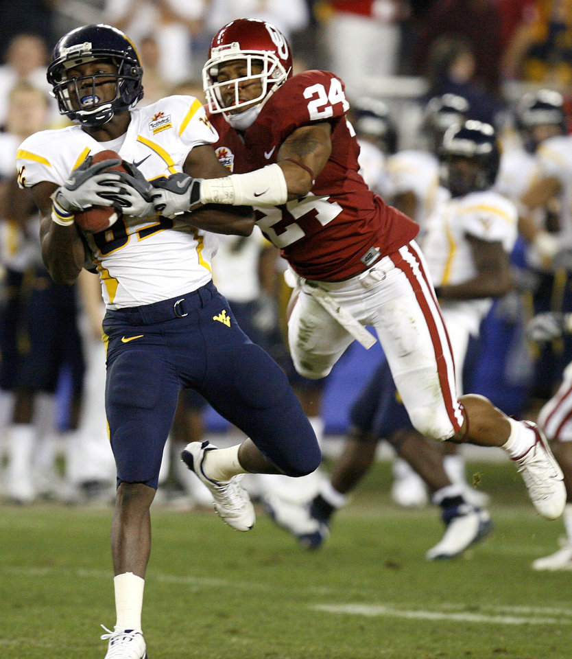 Photo - West Virginia's Tito Gonzales (83) pulls in a touchdown pass in front of Oklahoma's Marcus Walker (24) during the second half of the Fiesta Bowl college football game between the University of Oklahoma Sooners (OU) and the West Virginia University Mountaineers (WVU) at The University of Phoenix Stadium on Wednesday, Jan. 2, 2008, in Glendale, Ariz.   BY NATE BILLINGS, THE OKLAHOMAN ORG XMIT: KOD