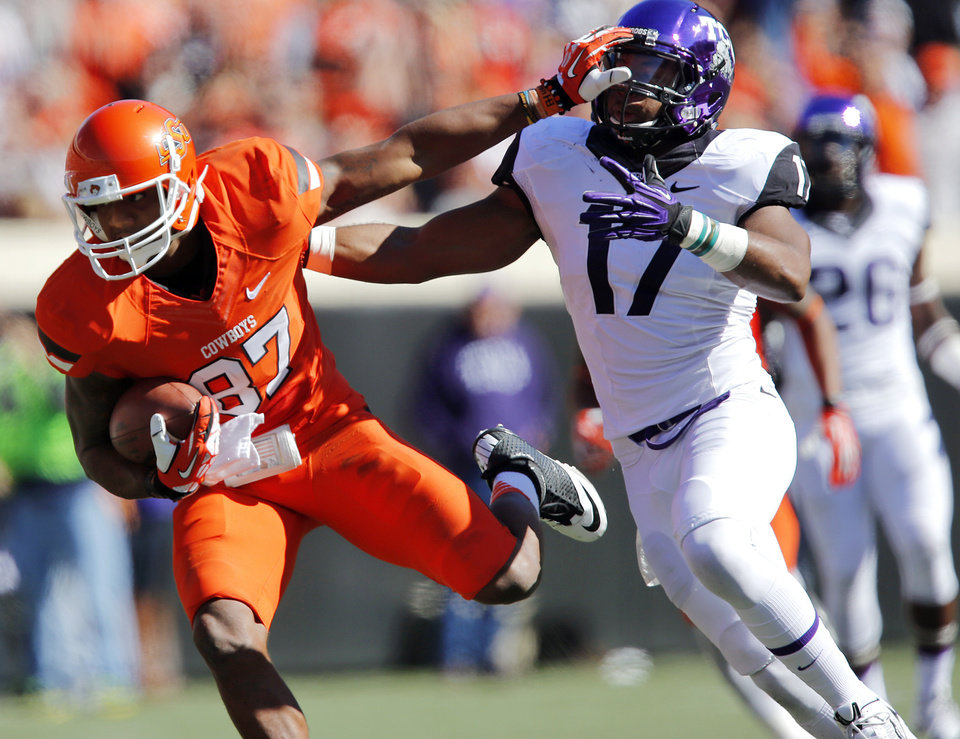 Oklahoma State\'s Tracy Moore (87) stiff arms TCU\'s Sam Carter (17) after a catch during a college football game between the Oklahoma State University Cowboys (OSU) and the Texas Christian University Horned Frogs (TCU) at Boone Pickens Stadium in Stillwater, Okla., Saturday, Oct. 19, 2013. Photo by Chris Landsberger, The Oklahoman