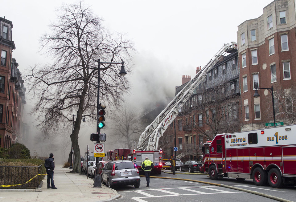 Photo - Firefighters fight a multi-alarm fire at a four-story brownstone in the Back Bay neighborhood near the Charles River, Wednesday, March 26, 2014, in Boston. Boston EMS spokesman Nick Martin says four people, including at least three firefighters, have been taken to hospitals. (AP Photo/Scott Eisen)