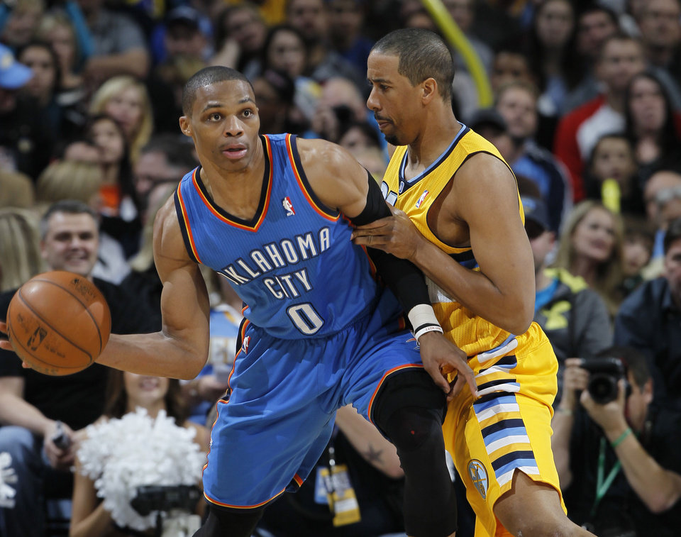 Oklahoma City Thunder guard Russell Westbrook, left, looks to pass under pressure from Denver Nuggets guard Andre Miller in the third quarter of an NBA basketball game in Denver on Sunday, Jan. 20, 2013. The Nuggets won 121-118 in overtime. (AP Photo/David Zalubowski)