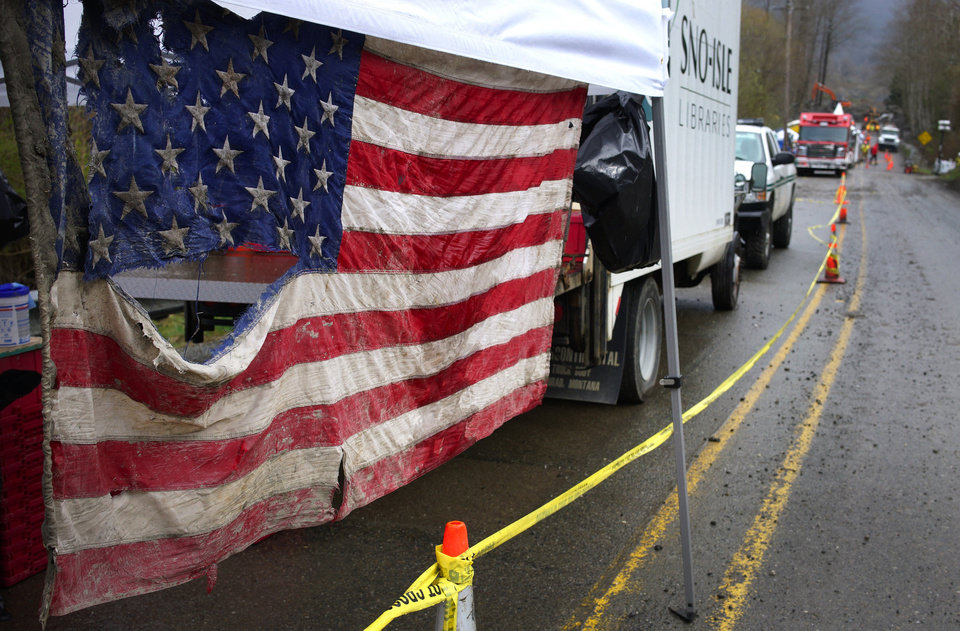 Photo - An American flag pulled from the debris hangs in the staging area at the west side of the mudslide on Highway 530 near mile marker 37, in Arlington, Wash., on Sunday, March 30, 2014. Periods of rain and wind have hampered efforts the past two days, with some rain showers continuing today. Last night, the confirmed fatalities list was updated to 18, with the number of those missing falling from 90 to 30. (AP Photo/Rick Wilking, Pool)
