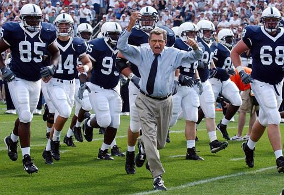 Photo - Penn State coach Joe Paterno leads his team onto the field before the game against Akron on Saturday, Sept. 4, 2004, in State College, Pa. Penn State won 48-10. (AP Photo /Carolyn Kaster)