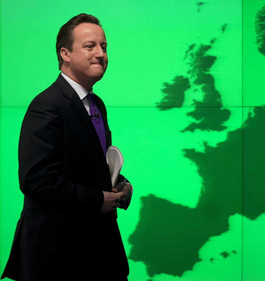Photo - Britain's Prime Minister David Cameron walks past a map of Europe on a screen as he walks away after making a speech on holding a referendum on staying in the European Union in London, Wednesday, Jan. 23, 2013. Cameron said Wednesday he will offer British citizens a vote on whether to leave the European Union if his party wins the next election, a move which could trigger alarm among fellow member states. He acknowledged that public disillusionment with the EU is