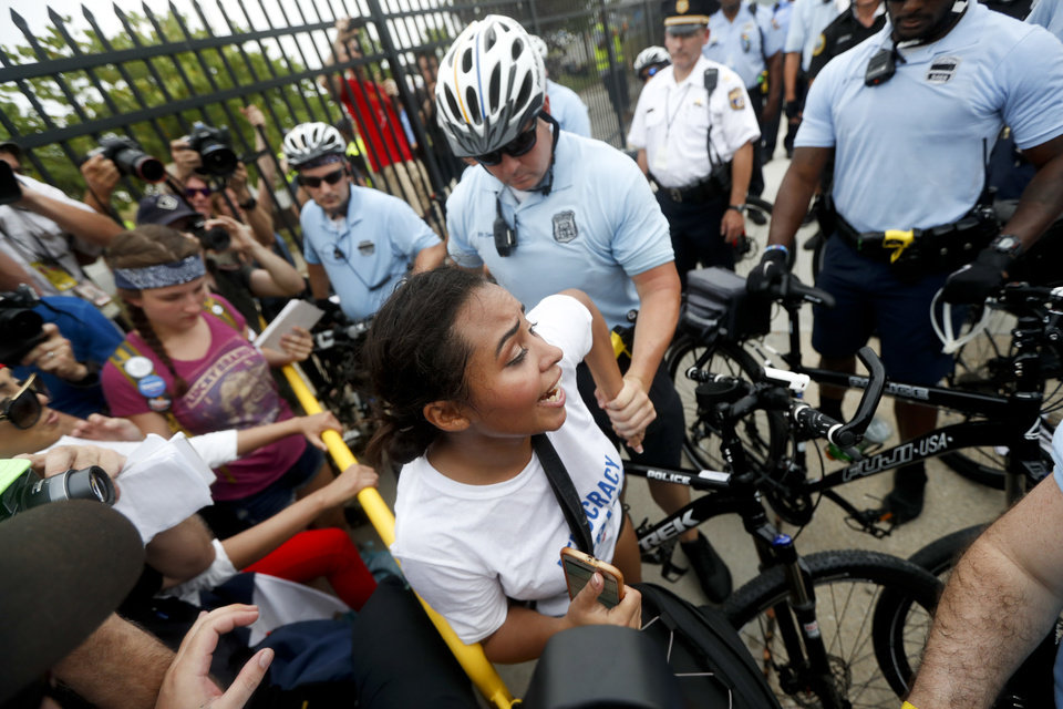 Photo - A demonstrator is taken into custody by police after climbing over a fence near the AT&T Station, Monday, July 25, 2016, in Philadelphia, during the first day of the Democratic National Convention. (AP Photo/John Minchillo)