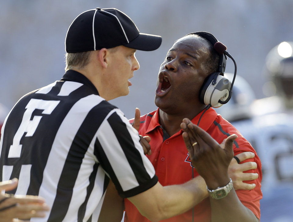 Photo - Liberty coach Turner Gill argues with an official during the first half of an NCAA college football game against North Carolina in Chapel Hill, N.C., Saturday, Aug. 30, 2014. (AP Photo/Gerry Broome)