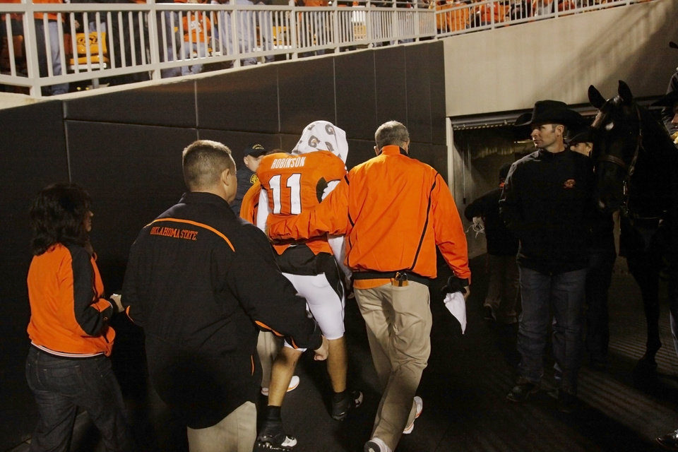 Photo - Zac Robinson is led off the field near the end of the game during the college football game between Oklahoma State University (OSU) and Texas Tech University (TT) at Boone Pickens Stadium in Stillwater, Okla. Saturday, Nov. 14, 2009. Photo by Doug Hoke, The Oklahoman