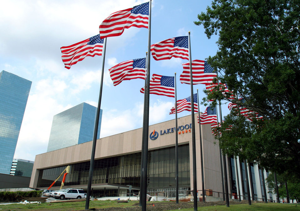 Photo - FILE - Flags fly in front of the Lakewood Church in this June 28, 2005 file photo in Houston. Authorities are investigating after $600,000 in checks and cash was stolen from a safe at Pastor Joel Osteen's Houston megachurch, which has one of the largest congregations in the country. Police spokesman Kese Smith said Tuesday March 11, 2014 $200,000 in cash and $400,000 in checks were stolen from a safe sometime between 2:30 p.m. Sunday and 8:30 a.m. Monday.  (AP Photo/Pat Sullivan, File)