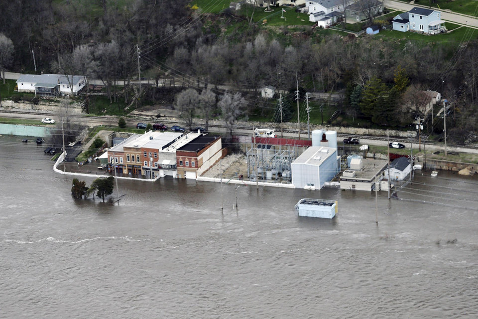 Photo - An aerial photo of Water Street in Peru, Ill., Friday, April 19, 2013, shows the Illinois River at record flood levels for the area. Restaurants such as Waterstreet Pub and Brandy's, pictured, prepared for the flooding Thursday by emptying out the lower levels of their businesses and building barricades of concrete, plastic tarp and sandbags.  Illinois Gov. Pat Quinn on Friday declared 38 counties as state disaster areas. He said reports indicate that conditions will get worse in the coming days. (AP Photo/NewsTribune, Genna Ord)