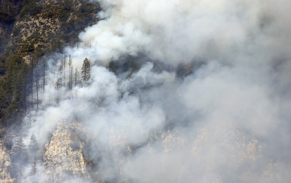 Photo - Windswept smoke from the Slide Fire pushes  up Oak Creek Canyon on Friday, May 23, 2014, near Flagstaff, Ariz.  The fire has burned approximately 7,500 acres and is five percent contained. (AP Photo/Ross D. Franklin)