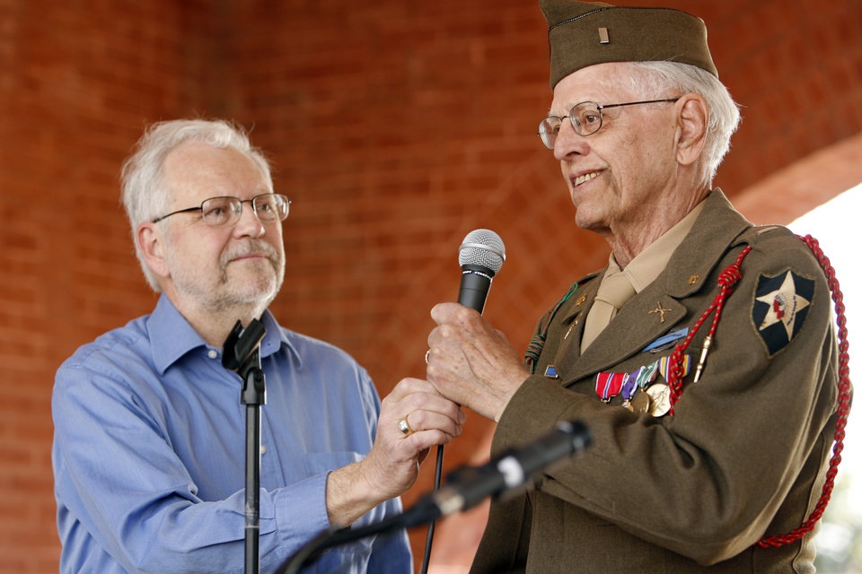 Photo - Jim Harvey hands the microphone to WWII veteran William Trumbly, 87, also of Norman as citizens hold a Tax Day Tea Party at the Santa Fe Station in Norman, Okla. on Wednesday, April 15, 2009.  