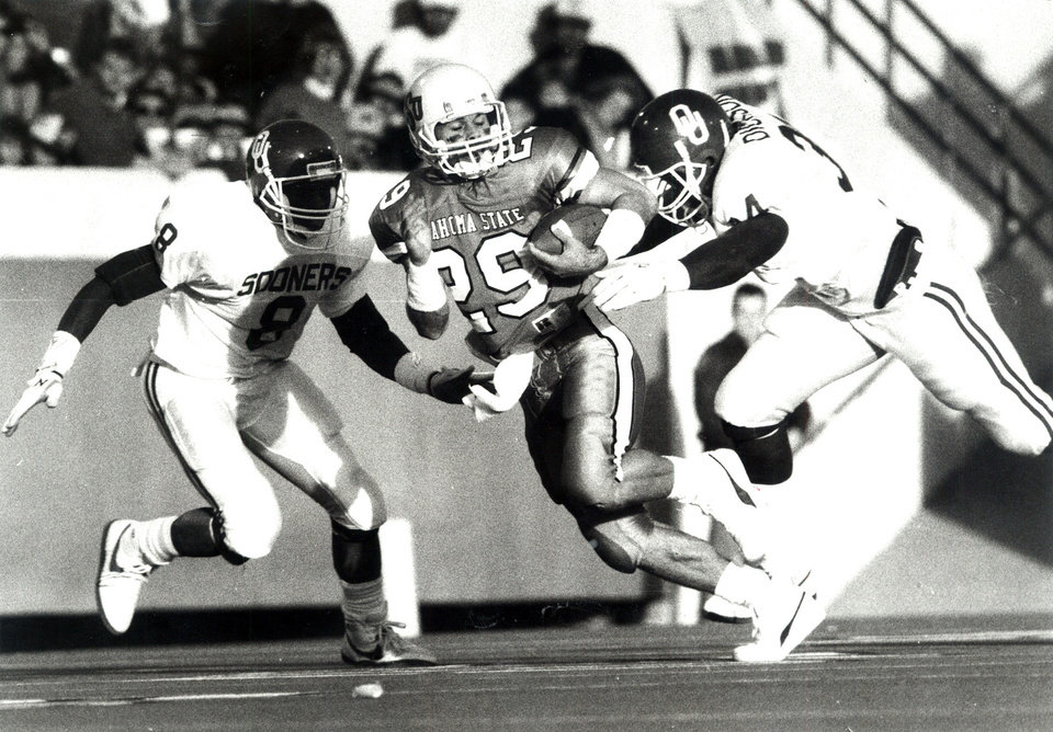 Brent Parker (center) of Oklahoma State University is chased by two Oklahoma Sooners during the 1988 Bedlam college football game. Scanned from Photo by Paul Hellstern, The Oklahoman