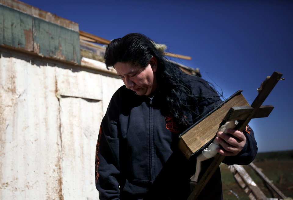 Irma Sanchez reacts after finding the family bible at their brother\'s mobile home at the Hideaway mobile home park, Sunday, April, 15, 2012, in Woodward, Okla. A tornado struck Woodward early Sunday morning. Photo by Sarah Phipps, The Oklahoman.