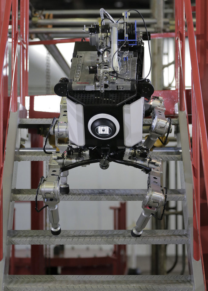Toshiba Corp.'s nuclear Inspection robot climbs stairs during a demonstration at a Toshiba factory in Yokohama, west of Tokyo, Wednesday, Nov. 21, 2012. The four-legged robot is designed to help at the meltdown-crippled Japanese nuclear plant, climbing over debris and venturing into radiated areas off-limits to human workers. (AP Photo/Itsuo Inouye)