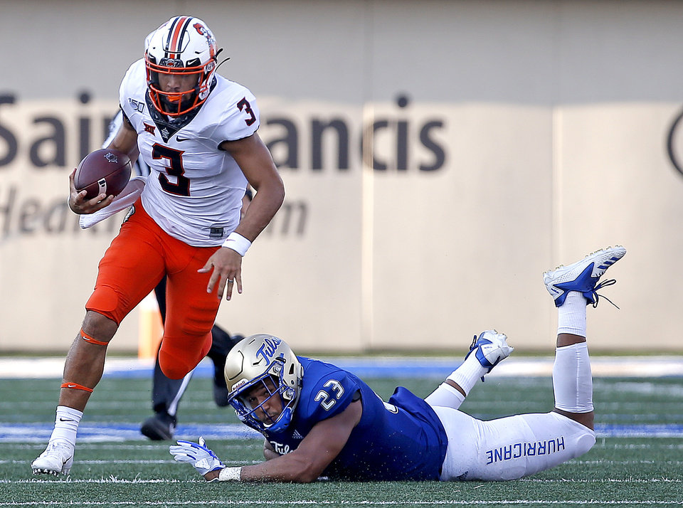 Photo - Oklahoma State's Spencer Sanders (3) gets by Tulsa's Zaven Collins (23) in the fourth quarter during a college football game between the Oklahoma State University Cowboys (OSU) and the University of Tulsa Golden Hurricane (TU) at H.A. Chapman Stadium in Tulsa, Okla., Saturday, Sept. 14, 2019. [Sarah Phipps/The Oklahoman]