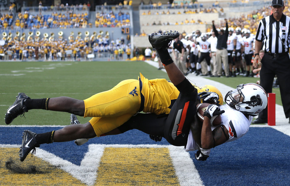 Photo - West Virginia's Karl Joseph (8) breaks up a pass intended for Oklahoma State's Josh Stewart (5) in the fourth quarter of a college football game between the Oklahoma State University and West Virginia University on Mountaineer Field at Milan Puskar Stadium in Morgantown, W. Va.,   Saturday, Sept. 28, 2013. Photo by Sarah Phipps, The Oklahoman