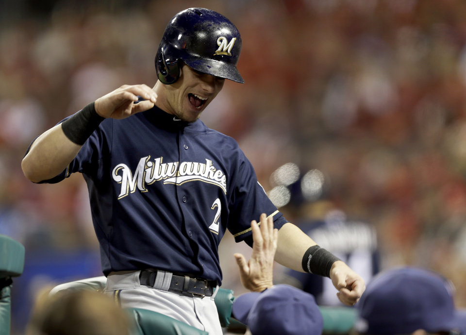Photo - Milwaukee Brewers' Scooter Gennett is congratulated by teammates as he enters the dugout after scoring on a single by Lyle Overbay during the fourth inning of a baseball game against the St. Louis Cardinals, Tuesday, April 29, 2014, in St. Louis. (AP Photo/Jeff Roberson)