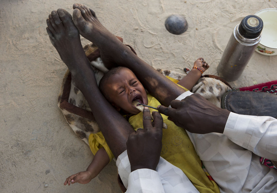 In this Nov. 5, 2012 photo, traditional healer Hakki Hassan cuts out the epiglottis of 8-month-old Moustafa Abdallah Lamine before also removing four un-erupted baby teeth as a treatment for vomiting and diarrhea, in Moussoro, Chad. In this Sahel nation, childhood malnutrition and related mortality persist at alarming rates, despite the fact that many affected families live within a day's journey of internationally-funded nutrition clinics. One reason is that families, bound by local custom, choose instead to seek traditional treatments, treatments which can lead to the very infections that kill their undernourished children. (AP Photo/Rebecca Blackwell)