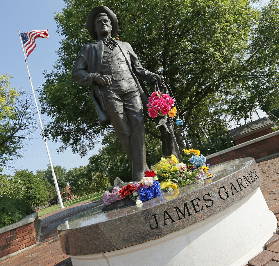 Photo - Flowers rest on the statue of James Garner on Main St. in downtown Norman, Okla., Sunday, July 20, 2014. Garner died Saturday at age 86. Photo by Nate Billings, The Oklahoman