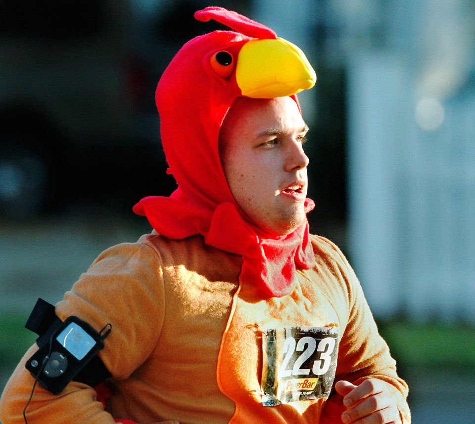 Photo - Wearing a turkey costume, Devon McNew of McLoud, nears the end of the 5K run as he sprints along Boulevard   during the annual Turkey Trot in downtown Edmond Thursday morning,  Nov. 24, 2011.  He said it was his first time to participate in the Turkey Trot .  Photo by Jim Beckel, The Oklahoman