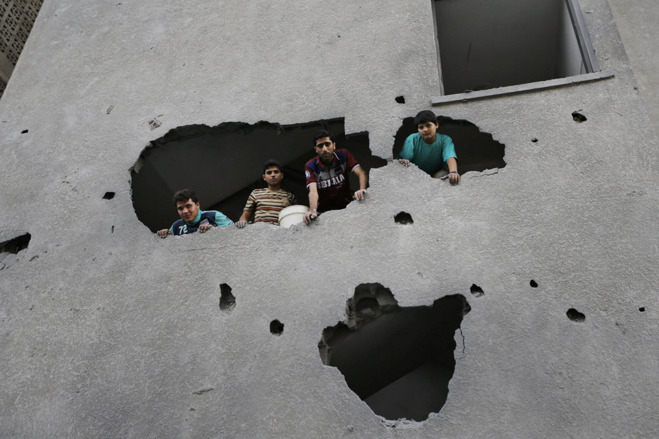 Photo - Palestinians from a damaged apartment building inspect the damage to a neighboring building, the offices of the Hamas movement's Al-Aqsa satellite TV station, in Gaza City, northern Gaza Strip, destroyed by an Israeli strike, Tuesday, July 29, 2014. Early Tuesday, Israel warplanes struck a series of targets in Gaza City, including the top Hamas leader in Gaza, Ismail Haniyeh's house and government offices, while Gaza's border area with Israel was hit by heavy tank shelling. (AP Photo/Lefteris Pitarakis)