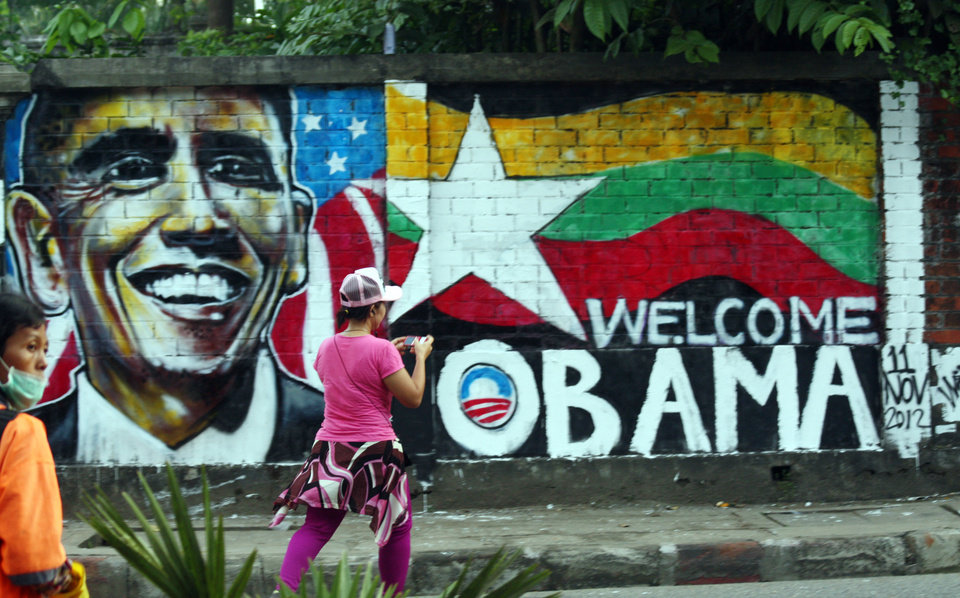 Photo -   A woman takes a photo of a wall painting created by Myanmar graffiti artists to welcome U.S. President Barack Obama on a street in Yangon, Myanmar, Saturday, Nov. 17, 2012. Obama will visit Myanmar on Monday, in a first for a sitting U.S. president. White House officials on Thursday said he will use his visit