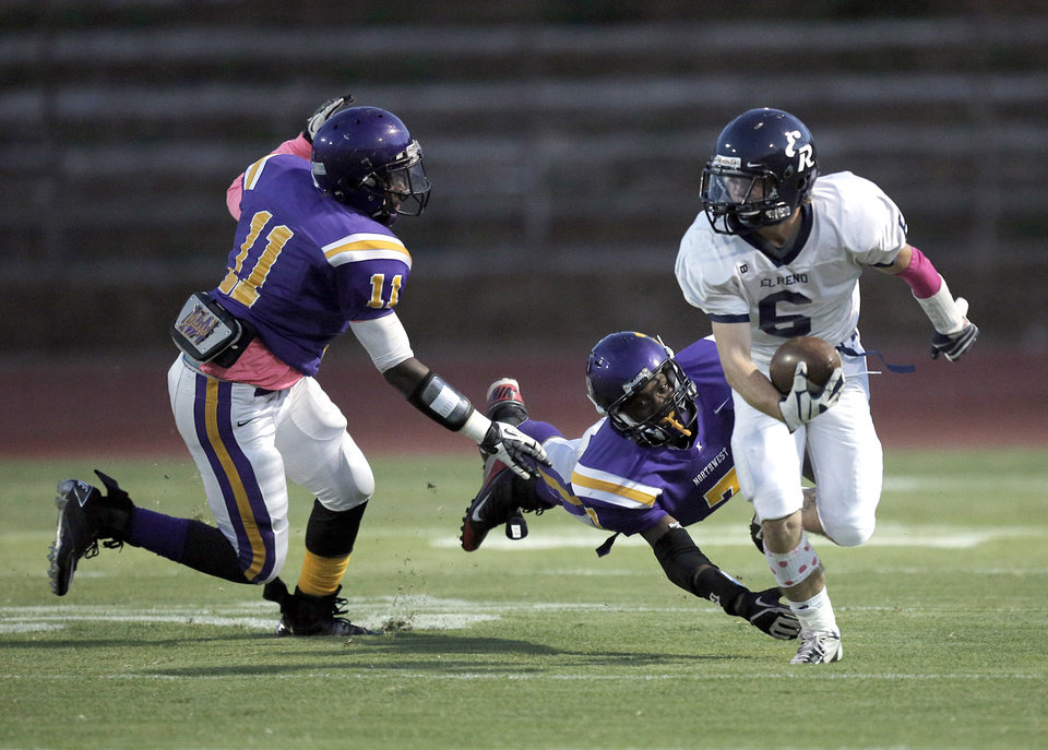 Photo - El Reno's Bailey Denny (6) runs from NWC's Damon Cozine (7) and Isaiah Beverly (11) during a high school football game between Northwest Classen and El Reno at Taft Stadium in Oklahoma City, Friday, Oct. 5, 2012.  Photo by Garett Fisbeck, The Oklahoman