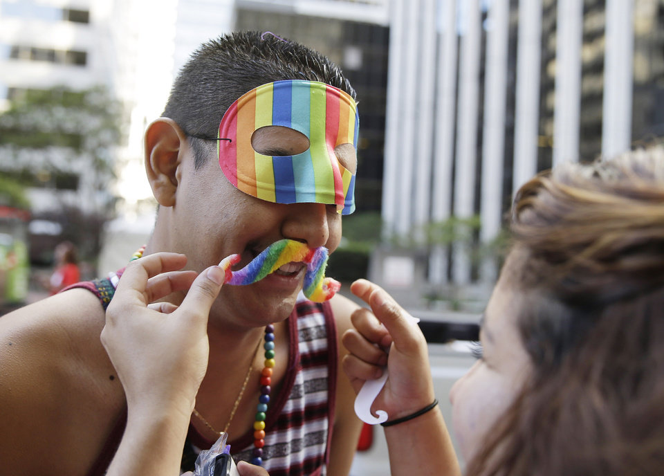 Photo - Christian Pacheco, left, of San Jose, Calif., gets help putting on his mustache from Flor Villartoro, right, before the start of the 44th annual San Francisco Gay Pride parade Sunday, June 29, 2014, in San Francisco. The lesbian, gay, bisexual, and transgender celebration and parade is one of the largest LGBT gatherings in the nation. The pair were marching with a group from Barefoot Wine. (AP Photo/Eric Risberg)