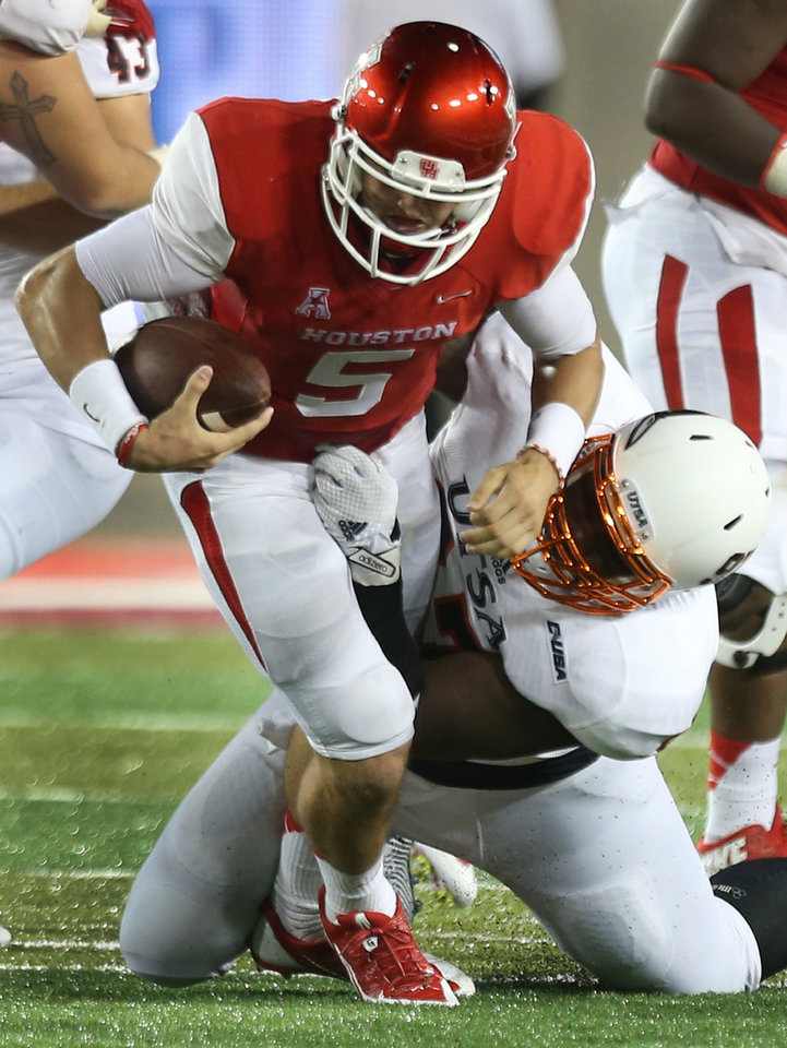 Photo - Houston quarterback John O'Korn (5) is sacked by UTSA defensive tackle Ashaad Mabry (97) during the second quarter of an NCAA college football game Friday, Aug. 29, 2014, in Houston. (AP Photo/Houston Chronicle, Brett Coomer) MANDATORY CREDIT