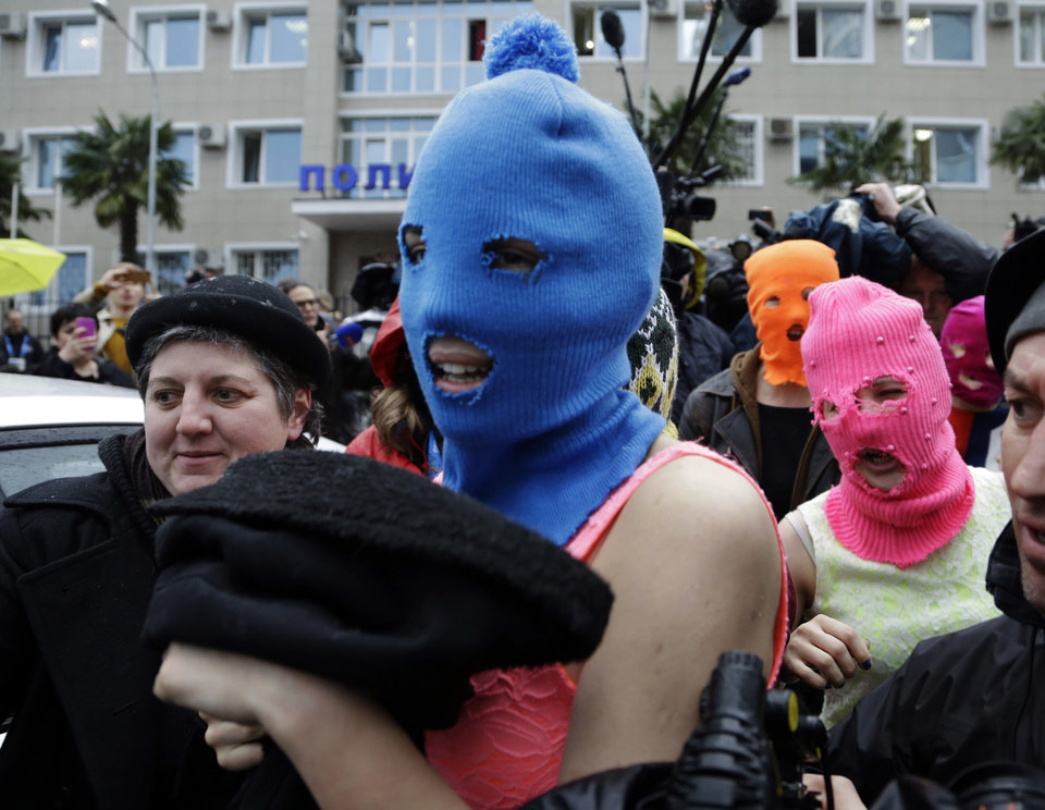 Photo - Russian punk group Pussy Riot members Nadezhda Tolokonnikova, in the blue balaclava, and Maria Alekhina, in the pink balaclava, make their way through a crowd after they were released from a police station, Tuesday, Feb. 18, 2014, in Adler, Russia. No charges were filed against Tolokonnikova and Alekhina along with the three others who were held. (AP Photo/Morry Gash)