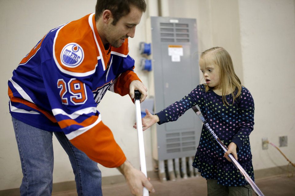 Photo - Mia Dickinson ,6, learns how to hold a hockey stick with her Barons Buddy Brad Hunt  during a Barons Buddies event with the Oklahoma City Barons and Special Olympians in Oklahoma City, Tuesday, November 5, 2013. The Special Olympians and their families were introduced to the Barons player that they will paired with throughout the year. Photo by Bryan Terry, The Oklahoman