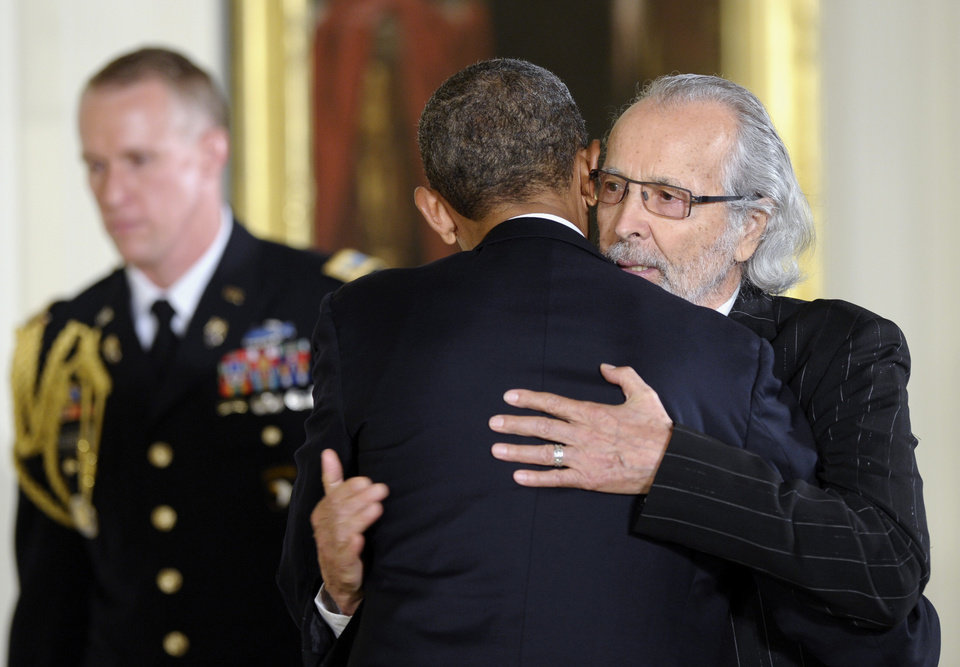 Photo - President Barack Obama hugs musician Herb Alpert before presenting him with the 2012 National Medal of Arts, Wednesday, July 10, 2013, during a ceremony in the East Room of White House in Washington. (AP Photo/Susan Walsh)