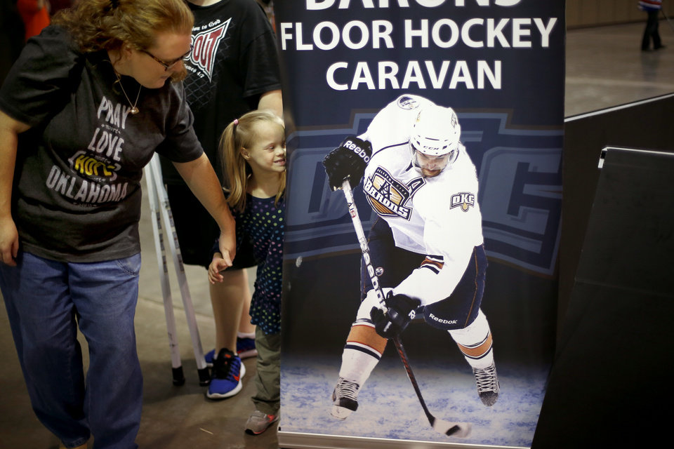 Photo -  Mia Dickinson ,6, looks at a Barons poster beside her mother Meghan Dickinson during a Barons Buddies event with the Oklahoma City Barons and Special Olympians in Oklahoma City, Tuesday, November 5, 2013. The Special Olympians and their families were introduced to the Barons player that they will paired with throughout the year. Photo by Bryan Terry, The Oklahoman