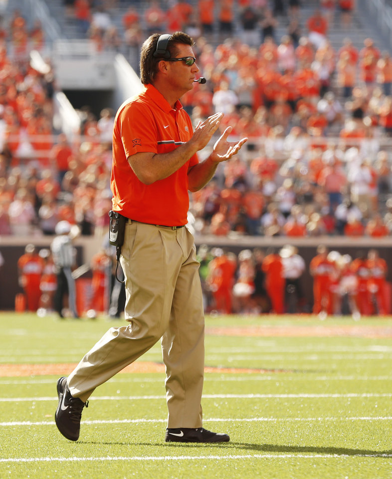 Photo - Oklahoma State head coach Mike Gundy walks to the end zone to congratulate the military family of the game during the second half of a college football game between the Oklahoma State Cowboys (OSU) and the Southeastern Louisiana Lions at Boone Pickens Stadium in Stillwater, Okla., Saturday, Sept. 12, 2015. Photo by Steve Sisney, The Oklahoman