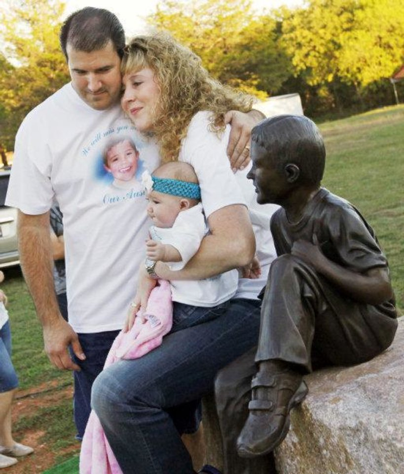 Photo - Jack Haley, left, and his wife, Renee Haley, embrace as she holds their daughter, Mikayla Haley, 6 months, next to a life-sized statue of their deceased son, Austin Haley, after the unveiling of the statue at the Haley family's home in Noble, Okla., Monday, Oct. 24, 2011. Five-year-old Austin Haley was killed by a Noble police officer's stray bullet in August of 2007. Austin Haley would have been ten years-old on Oct. 24, 2011. Photo by Nate Billings, The Oklahoman ORG XMIT: KOD