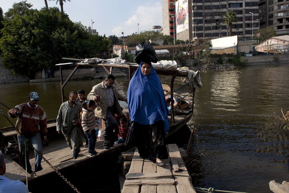 Photo - An Egyptian family leaves a ferry boat that is used by residents to cross the Nile river onto the Qursaya island, in Cairo, Egypt, Monday, Jan. 14, 2013. The Egyptian Armed Forces claims that it is the registered owner of the island's land, a claim disputed by the some 5,000 farmers and fishermen residents of the embattled island that have been resisting their eviction since 2007. (AP Photo/Nasser Nasser)