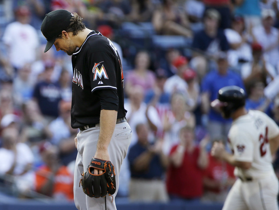 Photo - Miami Marlins starting pitcher Nathan Eovaldi, left, stands on the mound after giving up a home run to Atlanta Braves' Evan Gattis, right, in the second inning of a baseball game, Sunday, Aug. 31, 2014, in Atlanta. (AP Photo/David Goldman)