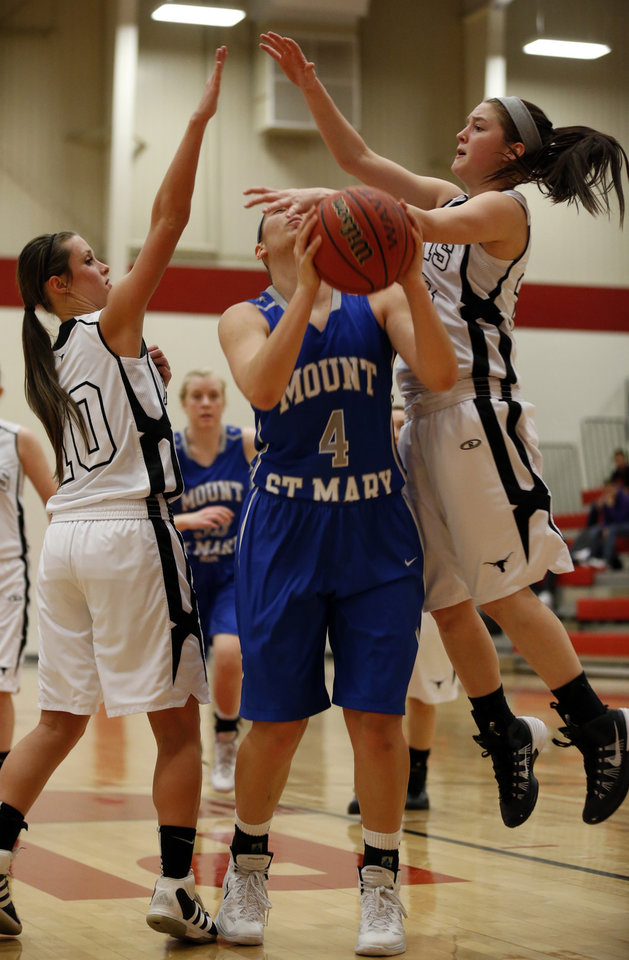 Photo - Mount St. Mary's Jordan Braun is fouled by Lone Grove's Madison Jones, right, as she shoots between Jones and Haley McCutchen during the Heart of Oklahoma Basketball Tournament on Thursday, Jan. 23, 2014, in Purcell, Okla.  Photo by Steve Sisney, The Oklahoman