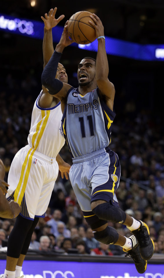 Photo - Memphis Grizzlies' Mike Conley, right, shoots against Golden State Warriors' Jarrett Jack during the second half of an NBA basketball game Wednesday, Jan. 9, 2013, in Oakland, Calif. (AP Photo/Ben Margot)