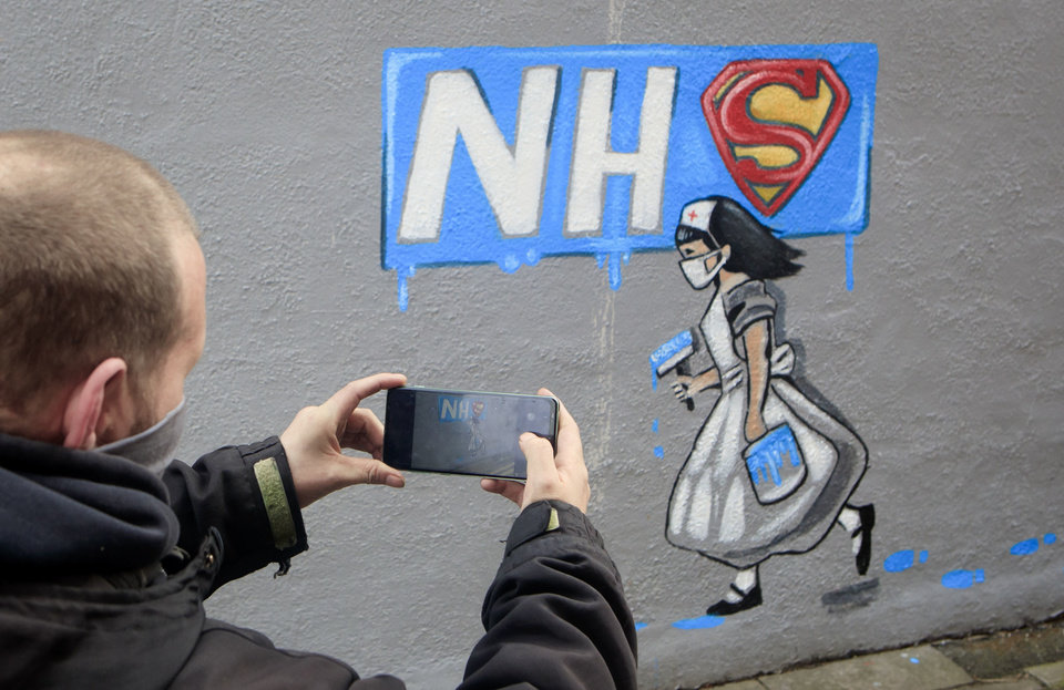 Photo -  A man takes a photograph of mural on the side of Horse Vaults pub in honour of the NHS amid the growing coronavirus outbreak, in Pontefract, England, Friday April 3, 2020. (Danny Lawson/PA via AP)