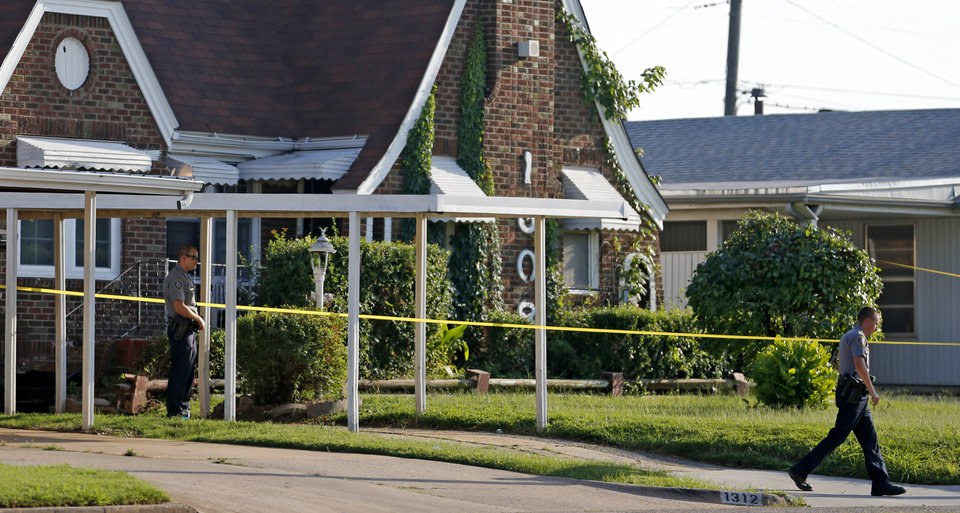 Photo - Oklahoma City Police stand outside a home in the 1300 block of NE 24 after an officer shot and killed a man in Oklahoma City, Wednesday, July 22, 2015. Photo by Bryan Terry, The Oklahoman