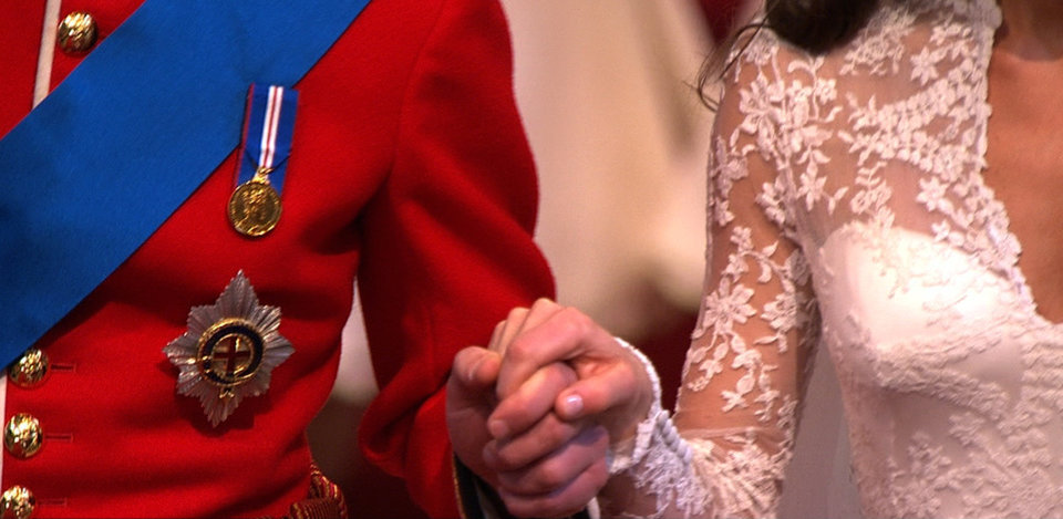 Photo - In this image taken from video, Britain's Prince William, left, holds the hand of his wife, Kate, the Dutchess of Cambridge, as they walk down the aisle together at Westminster Abbey for the Royal Wedding in London on Friday, April, 29, 2011. (AP Photo/APTN) EDITORIAL USE ONLY NO ARCHIVE PHOTO TO BE USED SOLELY TO ILLUSTRATE NEWS REPORTING OR COMMENTARY ON THE FACTS OR EVENTS DEPICTED IN THIS IMAGE ORG XMIT: RWVM303