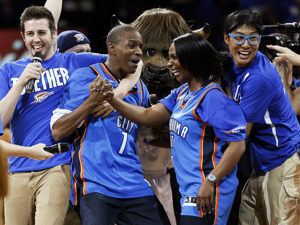 Photo - Larry Hill, 26, of Oklahoma City, second from left, reacts after hitting the $20,000 half-court shot during Game 1 in the first round of the NBA playoffs between the Oklahoma City Thunder and the Houston Rockets at Chesapeake Energy Arena in Oklahoma City, Sunday, April 21, 2013. Oklahoma City won, 120-91. Photo by Nate Billings, The Oklahoman