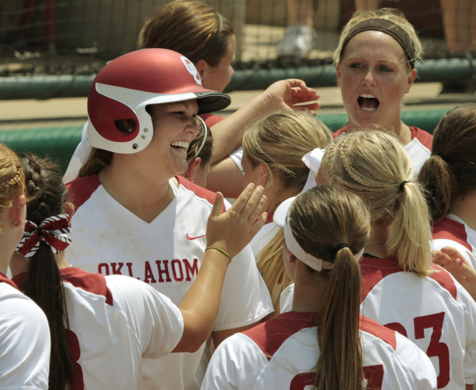 Photo - Katie Norris (with helmet) is greeted at home after a home run as the University of Oklahoma (OU) softball team plays Arizona in a super regional matchup at Marita Hines Field at OU on Friday, May 25, 2012, in Norman, Okla.  Photo by Steve Sisney, The Oklahoman