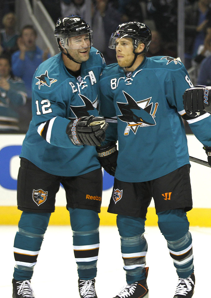 San Jose Sharks center Patrick Marleau (12) celebrates with Joe Pavelski (8) after scoring a goal against the Phoenix Coyotes during the first period an NHL hockey game in San Jose, Calif., Saturday, Oct. 5, 2013. (AP Photo/Tony Avelar)