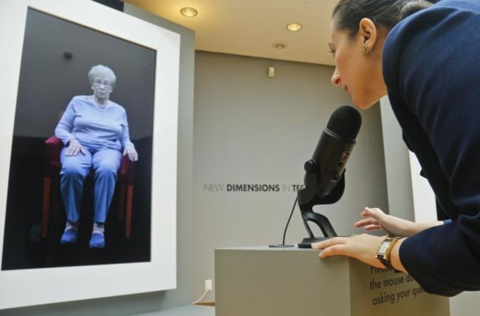 Photo -  In this 2017 photo, Josephine Mairzadeh uses a microphone to pose a question to a virtual presentation of Holocaust survivor Eva Schloss,  featured in a testimonial interactive installation called