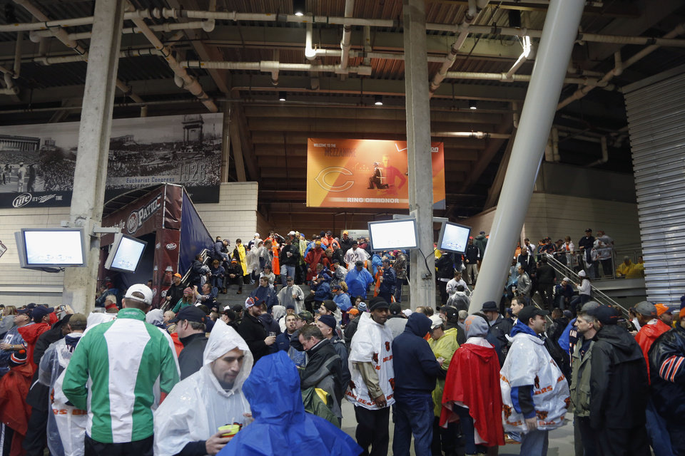 Photo - Fans seek shelter in the concourse area at Soldier Field as a severe storm blows through the area during the first half of an NFL football game between the Chicago Bears and Baltimore Ravens, Sunday, Nov. 17, 2013, in Chicago. Play was suspended in the game. (AP Photo/Charles Rex Arbogast)