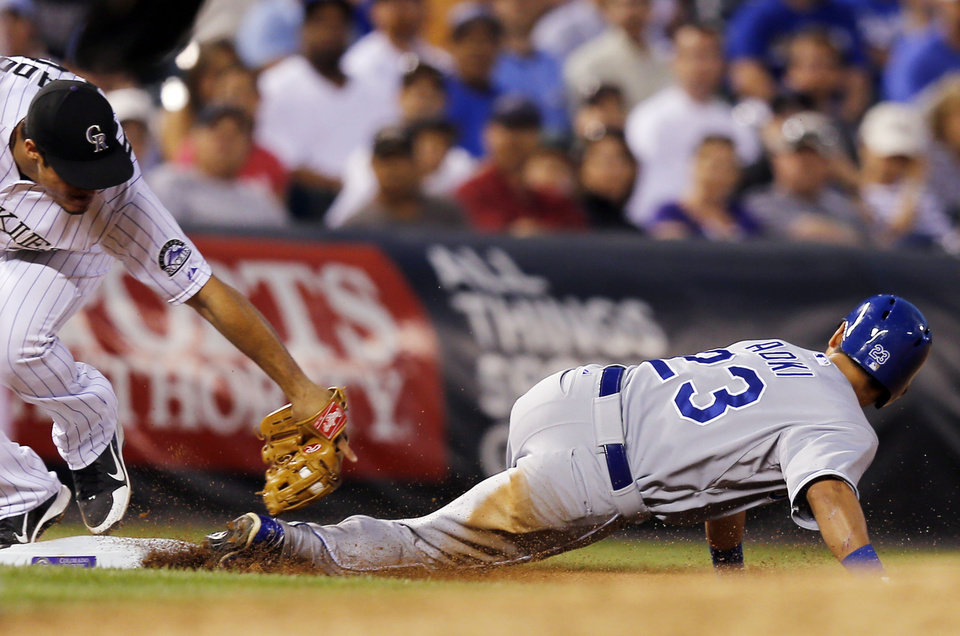 Photo - Kansas City Royals' Norichika Aoki (23) is tagged out on an attempted steal by Colorado Rockies third baseman Nolan Arenado (28) during the fifth inning of a baseball game Tuesday, Aug. 19, 2014, in Denver. (AP Photo/Jack Dempsey)