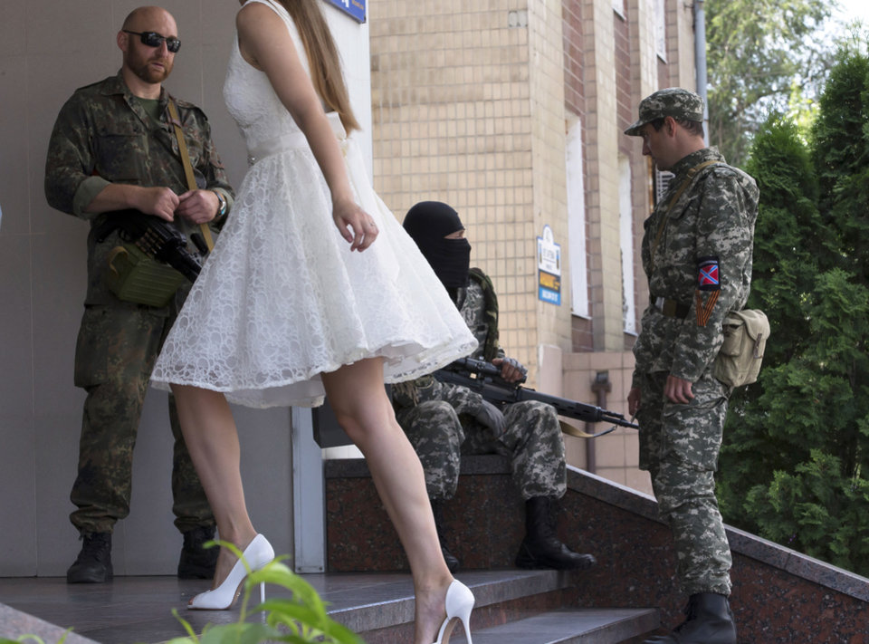 Photo - A woman walks past pro-Russian fighters talking outside after the wedding ceremony of Donetsk People's Republic platoon commander Arsen Pavlov and Elena Kolenkina in the city of Donetsk, eastern Ukraine Friday July 11, 2014. (AP Photo/Dmitry Lovetsky)